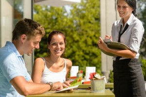 Couple at cafe ordering from menu waitress