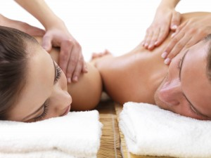 Close up of man and woman getting massage together, on romantic holiday at the spa.